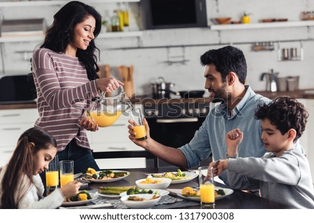 happy latin mother smiling while pouring orange juice during lunch near hispanic family #1317900308
