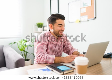 Happy latin salesman sitting at his home office desk and chatting during a videocall with co-workers