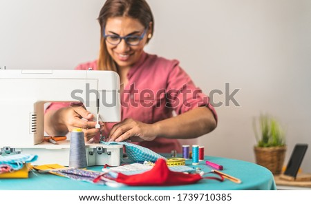 Happy Latin tailor seamstress woman sewing with machine homemade medical face mask for preventing and stop corona virus spreading - textile industry and covid19 healthcare concept