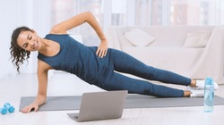 Happy Latin woman doing side plank exercise while watching workout video on laptop at home