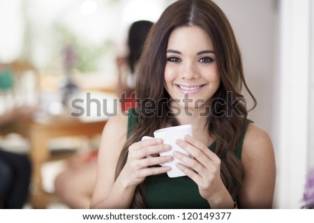 Happy latin woman drinking a cup of coffee at a restaurant