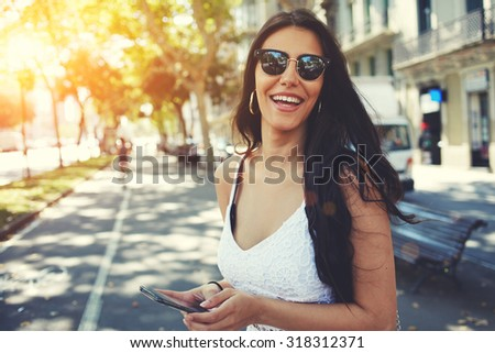 Photo of Happy Latin woman in summer sun glasses smiling brightly while holding smart phone strolling outdoors in the city at sunny day,female person using mobile standing with composition copy space on a side