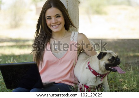 Happy latin woman spending time with her dog at the park