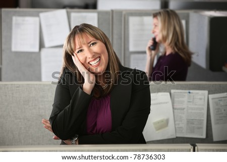Happy Latina office worker rests a hand on her face - stock photo
