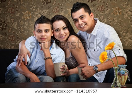 Happy Latino family hugging each other indoors
