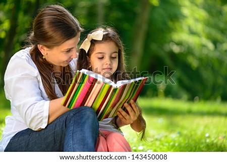 Happy Latino Family Reading Book At Park