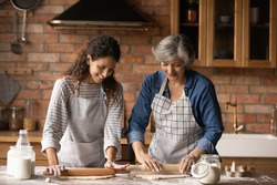 Happy Latino senior mother and grownup daughter make dough prepare sweet pie or pastries at home on weekend. Smiling Hispanic mature mom and adult girl cooking baking in kitchen. Hobby concept.
