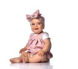 Happy laughing a bit sly infant baby girl in polka dot dress and headband with bow sits on the floor holding her hand at her knee. Happy infancy and babyhood concept