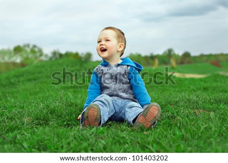 happy laughing baby boy sitting on green field