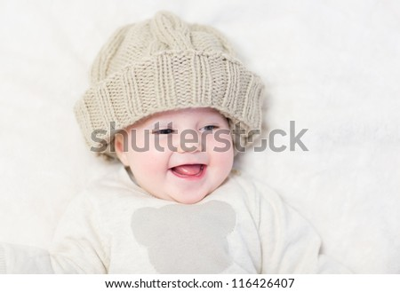 Happy laughing baby in a knitted hat