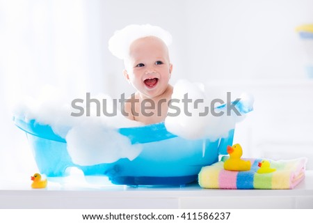 Happy laughing baby taking a bath playing with foam bubbles. Little child in a bathtub. Smiling kid in bathroom with colorful toy duck. Infant washing and bathing. Hygiene and care for young children. #411586237