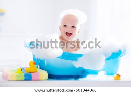 Happy laughing baby taking a bath playing with foam bubbles. Little child in a bathtub. Smiling kid in bathroom with colorful toy duck. Infant washing and bathing. Hygiene and care for young children. Сток-фото ©