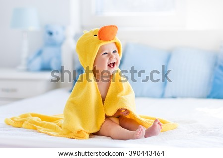 Photo of  Happy laughing baby wearing yellow hooded duck towel sitting on parents bed after bath or shower. Clean dry child in bedroom. Bathing and washing of little kids. Children hygiene. Textile for infants.