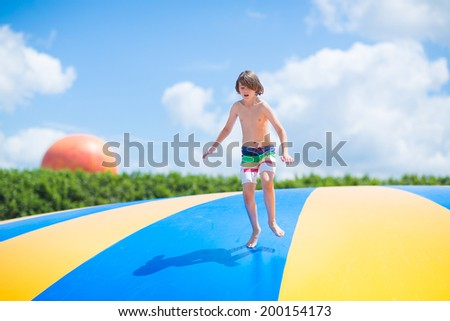 Happy laughing boy jumping on a colorful trampoline having fun at a party in a recreation park during summer vacation