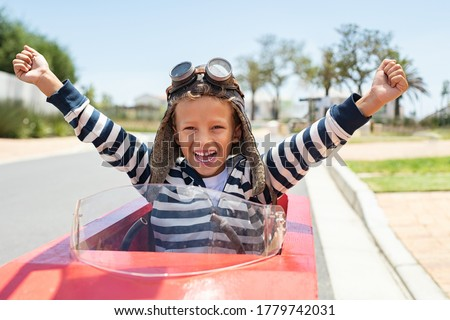 Photo of  Happy laughing boy raising hand in victory after riding gokart outdoor. KId having fun and driving toy race car on street. Child exult while riding an electric or peddle toy auto wearing pilot helmet.