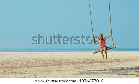 Happy laughing child girl swinging at tropical sandy beach. #1076677010