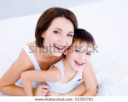 Happy  laughing faces of the young mother and her cute son sitting on a bed