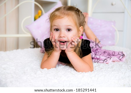 Happy laughing girl  on a bed