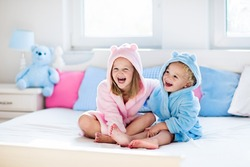 Happy laughing kids, boy and girl in soft bathrobe after bath play on white bed with blue and pink pillows in sunny bedroom. Child in clean and dry towel. Wash, infant hygiene, health and skin care