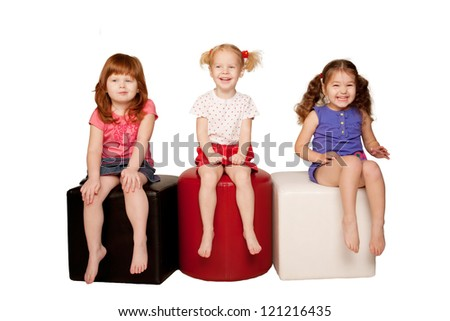 Happy laughing kids. Three beautiful girls sitting, looking at something and laughing. Isolated on white background