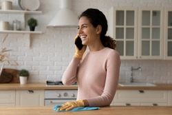 Happy laughing latina housewife take break in cleaning new modern kitchen furniture to answer phone call of good friend. Positive young woman enjoy talk chat on cell while doing daily household chores