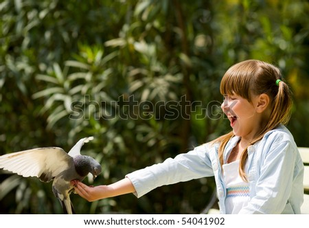 Happy laughing little girl feeding Pigeon sitting on hand