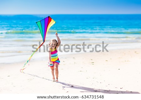 Happy laughing little girl flying a colorful kite running and jumping in sand on beautiful tropical beach during active summer family sea vacation. Kids play on ocean shore. Child with beach toys.