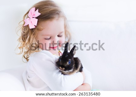 Happy laughing little girl playing with a baby rabbit, hugging her real bunny pet and learning to take care of an animal. Child on a white couch at home or kindergarten. stock photo