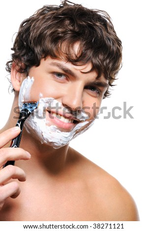 Happy laughing man shaving his face over white background