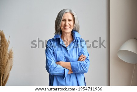 Happy laughing mature elder 60s business woman standing indoors. Senior mid age older stylish look woman portrait with crossed arms looking at camera at modern home office.