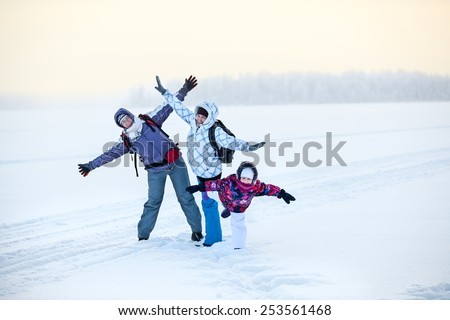 Happy laughing mature woman, young woman and girl posing on frozen winter lake