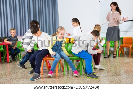 Happy laughing pupils of primary school having fun during break with their teacher, playing musical chairs