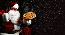 Happy laughing Santa Claus hold big hot steaming original pizza offering pointing finger under the snow with copy space. New year and Merry Christmas fast food concept banner