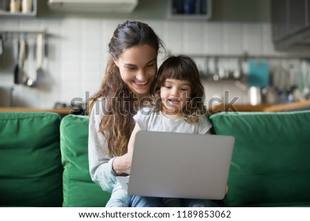 Happy laughing single mother and little preschool cute daughter using laptop online application, making video call, having fun, babysitter teaching small girl use computer, watching cartoons together #1189853062
