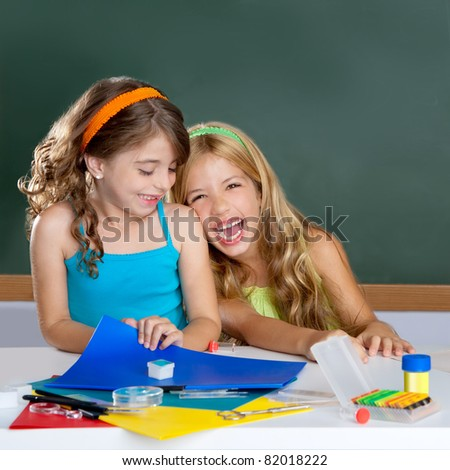 happy laughing student girls group at school classroom desk
