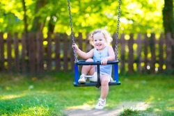 Happy laughing toddler girl with curly hair wearing a blue dress having fun on a swing enjoying a hot sunny summer day on a playground in a park