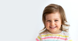 Happy laughing toddler kid girl wearing striped t-shirt portrait against neutral background