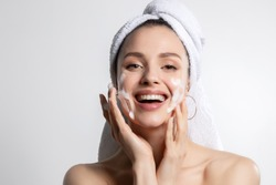 Happy laughing young caucasian woman wrapped in head towel washing face with foam soap cosmetic product. Everyday morning hygiene routine. Skincare and wellness, beauty and cosmetology. Portrait