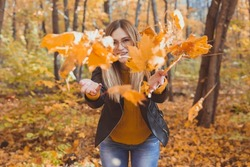 Happy laughing young woman throwing leaves in autumn park. Fall season