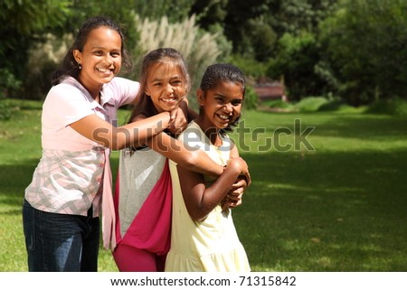 Happy laughter and hugs from three school friends