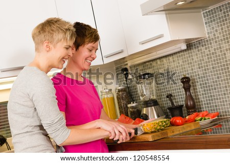 Happy lesbian couple making a breakfast in the kitchen, they cut a pineapple together
