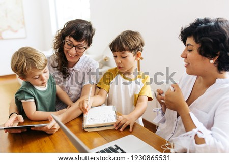 Happy LGBT family at home. Lesbian couple sitting with their kids using a digital tablet. Сток-фото ©