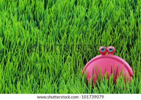 Happy lilac money purse on the green grass - stock photo