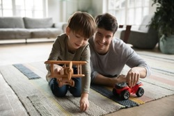 Happy little adorable kid boy playing with favorite plane toy with caring young father, sitting together in living room. Joyful different generations family having fun, enjoying playtime at home.