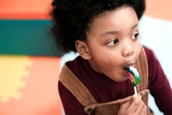 Happy little african american child boy eating candy lollipop. Black kid boy with curly hair and lollipop. Adorable black kid boy with colorful lollipop.