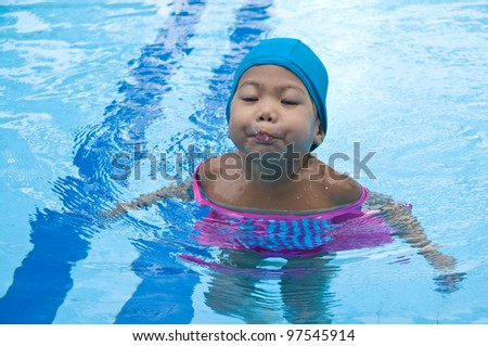 Happy little asia girl learning to swim in the pool.
