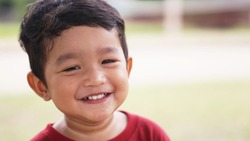 Happy Little Asian baby boy 2 years old. child showing teeth with big smile and laughing in Red T-shirt Healthy happy funny smiling face young toddler lovely kid concept.