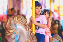 Happy little asian brother and sister funny and enjoying in funfair riding and smile on colorful carousel house