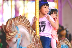 Happy little asian brother and sister funny and enjoying in funfair riding on colorful carousel house