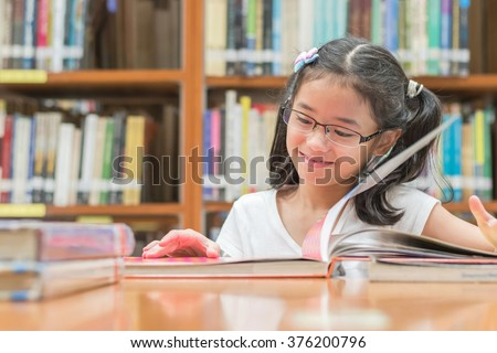 Happy little asian child girl w/ eyeglasses reading book school background: Lovely cute young female student kid opening flipping book in archive resource collection room: National library lover month